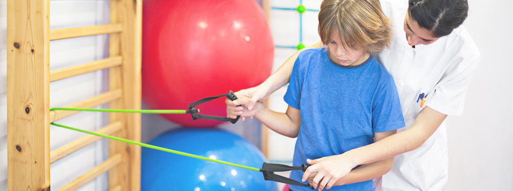 Image of a physical or occupational therapist working with resistance bands with a student and positioning the student's hands on the equipment.