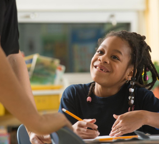 A girl sitting at a school desk looks up smiling at a teacher.